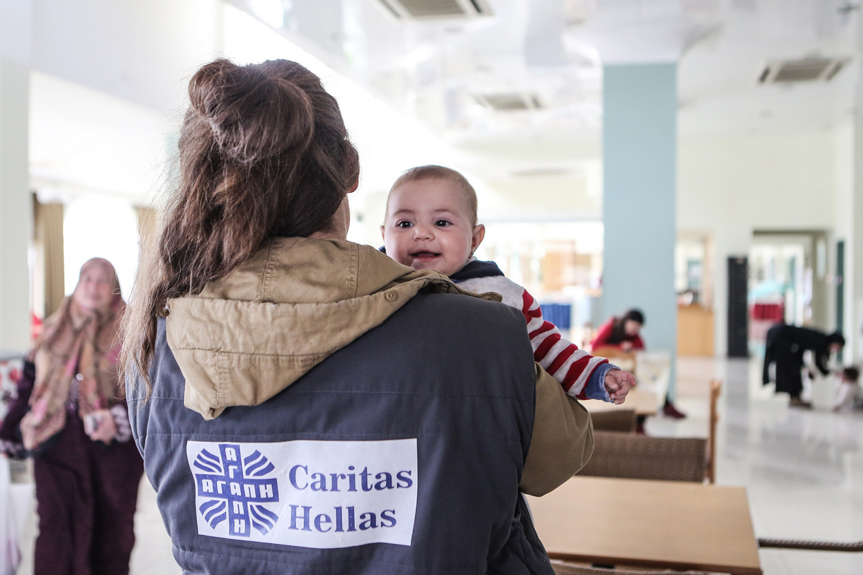Aid worker carrying baby at Caritas hotel in Lesbos. Photo by Lefteris Partsalis, Caritas Switzerland