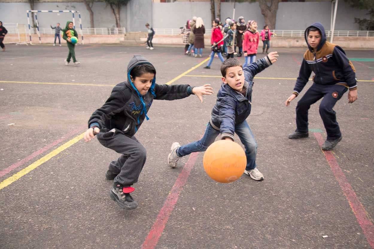 Students play football during recess
