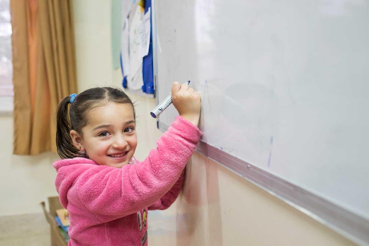 Un jeune élève impatient d'intervenir en classe