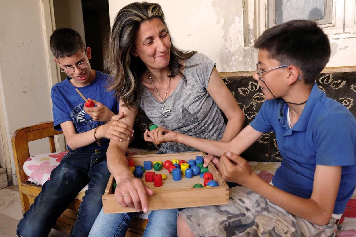 Busfira está criando a dos hijos discapacitados con ayuda de Caritas.